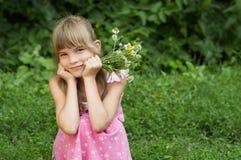 Das Mädchen sitzt mit dem Blumenstrauß Lizenzfreie Stockbilder