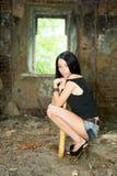 Das Mädchen sitzt mit einem Baseballschläger Stockfoto