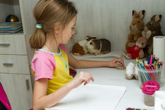 Das Mädchen sitzt am Tisch im Kind-` s Raum Lizenzfreies Stockbild