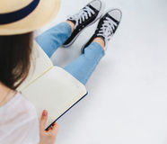 Das Mädchen sitzt und betrachtet das Buch Stockfotografie