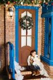 Das Mädchen sitzt unter der Tür Stockfotografie