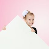 Das Mädchen späht heraus von hinten weiße Fahne Stockfoto