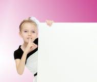 Das Mädchen späht heraus von hinten weiße Fahne Lizenzfreie Stockfotografie