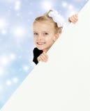 Das Mädchen späht heraus von hinten weiße Fahne Lizenzfreies Stockfoto