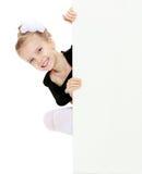 Das Mädchen späht heraus von hinten weiße Fahne Lizenzfreie Stockfotos