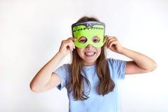 Das Mädchen spielt den Dummkopf in einer Maske des Monsters für Halloween Stockfotos