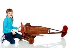 Das Mädchen spielt mit einem großen Spielzeugflugzeug Lizenzfreies Stockfoto