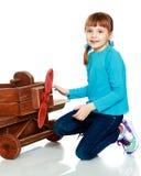 Das Mädchen spielt mit einem großen Spielzeugflugzeug Lizenzfreie Stockfotografie