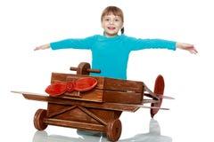 Das Mädchen spielt mit einem großen Spielzeugflugzeug Stockbild