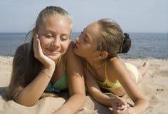 Das Mädchen spielt mit Sand auf einem Strand Lizenzfreies Stockfoto