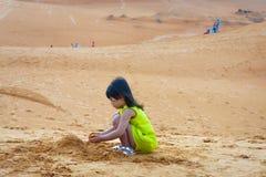 Das Mädchen spielt Spaß auf Sandstrand Lizenzfreie Stockfotos