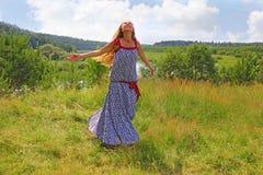 Das Mädchen spinnt auf das grüne Gras im Sommer Lizenzfreie Stockfotos