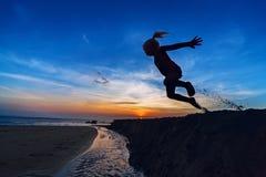 Das Mädchen springend auf den Sonnenuntergangstrand Stockfotos