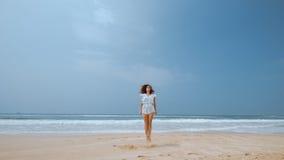 Das Mädchen springend auf den Strand nahe dem Ozean Lizenzfreie Stockfotos