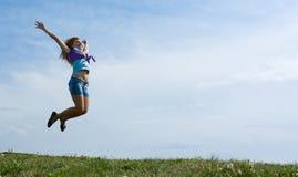 Das Mädchen springend auf die Wiese. Stockbilder
