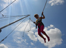 Das Mädchen springend auf eine Trampoline mit Seilen Lizenzfreies Stockfoto