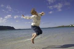 Das Mädchen springend auf Strand Lizenzfreies Stockbild