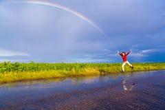 Das Mädchen springend auf nasse Straße mit Regenbogen Lizenzfreie Stockfotos