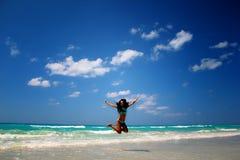Das Mädchen springend auf Strand Lizenzfreie Stockbilder