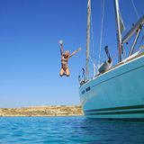 Das Mädchen springend in Meer weg vom Boot Stockbild