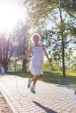 Das Mädchen springend mit Seilspringen Baum auf dem Gebiet Methode in der Stadt Stockbilder