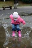 Das Mädchen springend in Pfützen stockbilder