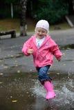 Das Mädchen springend in Pfützen Stockbild