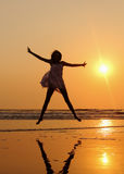 Das Mädchen springend am Strand Lizenzfreie Stockbilder