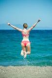Das Mädchen springend am Strand Lizenzfreie Stockfotos