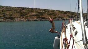 Das Mädchen springend von der Yacht in Meer Stockbild