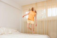 Das Mädchen springt in das Schlafzimmer Glückliches Kindermädchen, das Spaß hat stockfotografie