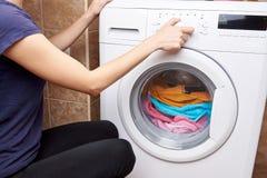 Das Mädchen startet eine Waschmaschine stockfoto