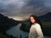 Das Mädchen steht auf einem Hintergrund des Sonnenuntergangs Stockfotografie