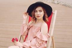 Das Mädchen steht auf einem Ruhesessel still Das Mädchen in einem schönen rosa Kleid, schwarzer moderner Hut steht auf einer Reis stockfotos