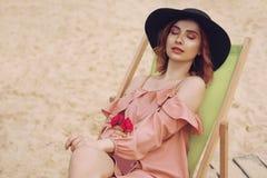 Das Mädchen steht auf einem Ruhesessel still Das Mädchen in einem schönen rosa Kleid, schwarzer moderner Hut steht auf einer Reis stockfoto