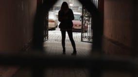 Das Mädchen steht in der Stadt auf der Straße im Bogen, modern stock footage