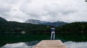 Das Mädchen steht mit ihren Armen, die vor ihr auf dem Pier von schwarzem See im Nationalpark Durmitor gekreuzt werden montenegro Lizenzfreie Stockfotos