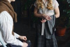 das Mädchen steht nahe bei dem Sitzkerl, sie sprechen, eine Weinleseart stockfoto