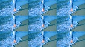 Das Mädchen steht nahe dem Meer und Wellen rollen sie auf ihren Füßen stock video footage