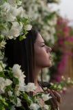Das Mädchen steht nahe der lebenden Wand von Blumen und blickt in Richtung der Dämmerung Stockfotos