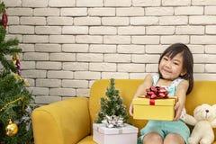 Das Mädchen stellt ein Weihnachtsgeschenk dar Mädchen, welches die Geschenkbox zeigt Nettes asiatisches Kind, das ein Weihnachtsg stockfotos