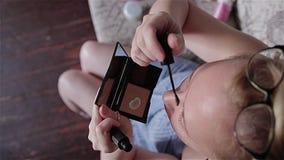 Das Mädchen tönt sich mit Augenbrauen und den Wimpern einer speziellen Bürste ab Die Ansicht von der Oberseite stock video footage