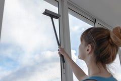 Das Mädchen in T-Shirt und blauen den kurzen Hosen des Türkises wäscht das Fenster stockfoto