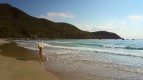 Das Mädchen trägt gelbes Surfbrett gehend entlang Seeküste stock video