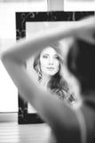 Das Mädchen trägt Ohrringe von den Spiegeln. Stockfoto
