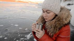 Das Mädchen trinkt Tee auf Eis stock video footage