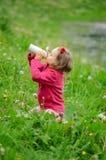 Das Mädchen trinkt Wasser von einer Thermosflascheflasche Becher-Thermosflaschen, Frühlingsgras, gelocktes Haar, Erholung im Frei stockbild