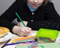 Das Mädchen tut die Lektionen, liegt auf dem Tisch ein Sandwich, Frucht, Nüsse, Lehrbücher, Bleistifte, Nosh Stockbild