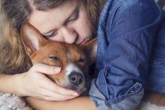 Das Mädchen umarmt den basenji Hund lizenzfreies stockfoto
