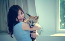 Das Mädchen umarmt den Fuchs Stockfotos